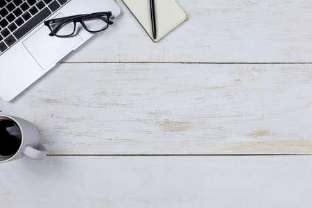 flacher Schreibtischtisch moderner Arbeitsplatz mit Laptop auf weißem Holztisch, Laptophintergrund mit Draufsicht und Kopienraum auf weißem Hintergrund, weißes Schreibtischbüro mit Laptop, Smartphone und anderen Arbeitsmaterialien mit Tasse Kaffee.