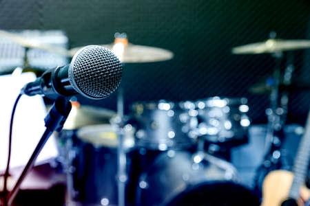 Microfono professionale da studio a condensatore, concetto musicale. registrazione, microfono con messa a fuoco selettiva in studio radiofonico, microfono con messa a fuoco selettiva e sfocatura dell'attrezzatura musicale chitarra, basso, sfondo del pianoforte a tamburo.