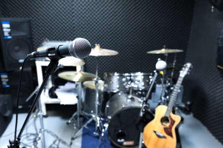 Microfono professionale da studio a condensatore, concetto musicale. registrazione, microfono con messa a fuoco selettiva in studio radiofonico, microfono con messa a fuoco selettiva e sfocatura dell'attrezzatura musicale chitarra, basso, sfondo del pianoforte a tamburo. Archivio Fotografico