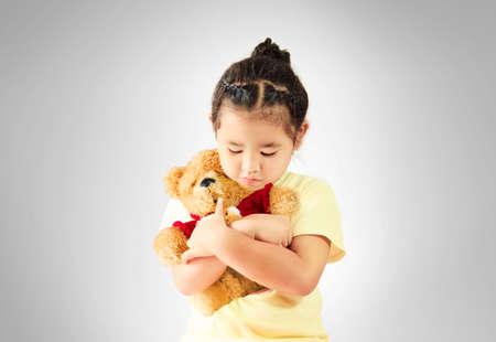 downcast: Sad little girl hugging teddy bear alone, studio shoot