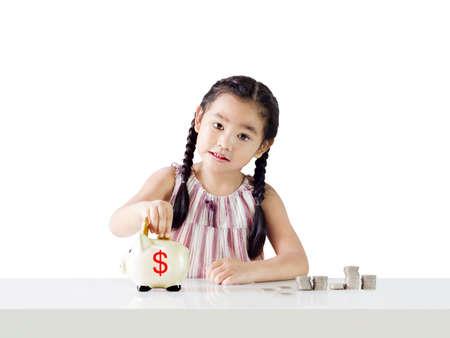 アジア女の子ピギー銀行、教育、お金の概念を節約お金を節約します。白い背景で隔離