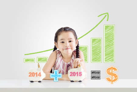 Little girl putting money on a piggy bank with a new year 2015.saving concept from 2014 until 2015 drawing Foto de archivo