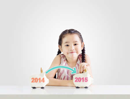 Little girl thinking about saving and putting money on a piggy bank with a new year 2015. photo
