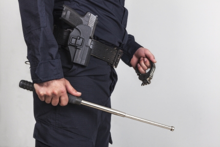 police equipment: Policeman with gun, handcuff and iron baton Stock Photo