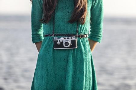 Vintage, brunette meisje met retro camera aan de zee Stockfoto