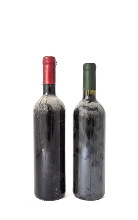 Old dusty wine bottles on white background photo