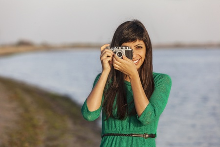 Vintage photo, brunette girl with retro camera by the sea