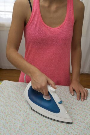 woman ironing: Woman ironing sheet with flowers Stock Photo