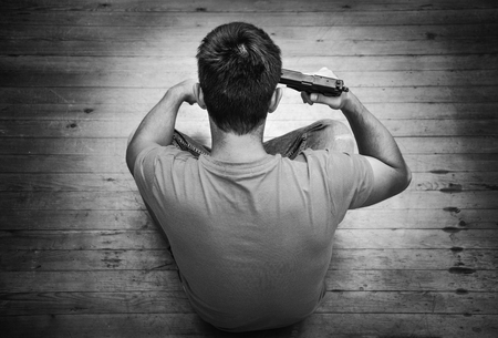 gun room: Man with pistol gun turned on his head wants to commit suicide, inside a house room. Black and white Stock Photo