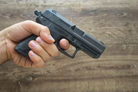asculine hand holding pistol gun, frond wooden background 스톡 콘텐츠