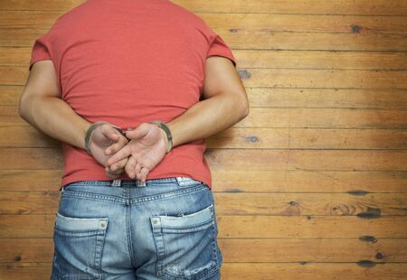 young  cuffs: Lying man on wooden dirty floor with handcuffs Stock Photo