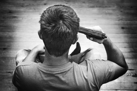Man met pistool pistool draaide op zijn hoofd wil om zelfmoord te plegen, in een huis kamer. Zwart en wit