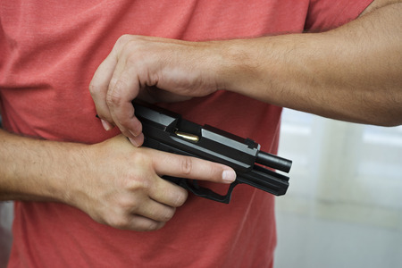 gun room: Man holding and load a gun pistol in a house room