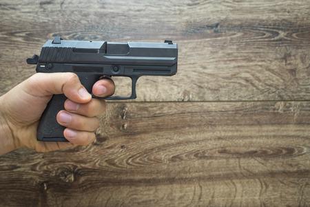 masculine: Masculine hand holding pistol gun, frond wooden background