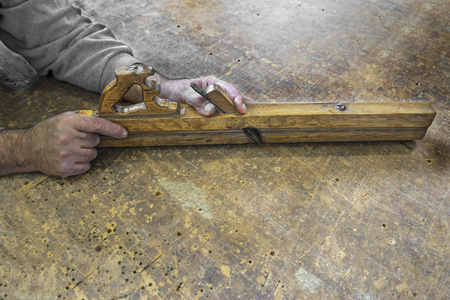 planer: Carpenters hands hold planer tool on a vintage wooden background