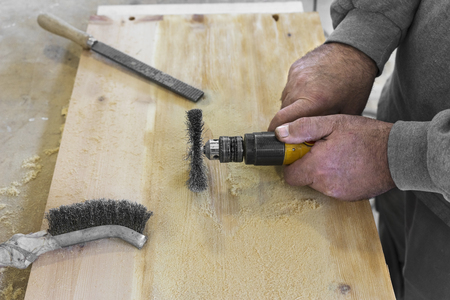 sanding: Hands man with electrical rotating brush metal disk sanding a piece of wood Stock Photo