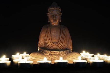 Houten standbeeld van Boeddha met kaarsen om hem heen Stockfoto