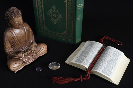 holy bible: Wooden statue of Buddha with koran and holy bible