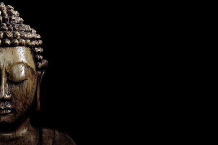 Wooden buddha statue on table shot in studio
