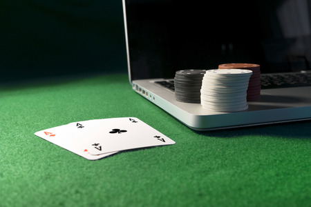 poker card: Laptop, poker cards and poker chips, on green background.