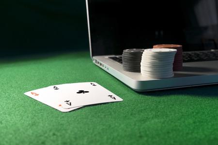 Laptop, poker kaarten en poker chips, op groene achtergrond. Stockfoto