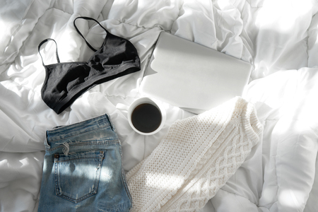 Female outfit, a  cup of coffee and a laptop laid out on bed, morning light Stock Photo