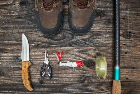fishing gear: fishing tackles and fishing gear on wooden background, top view
