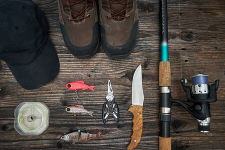 sport shoe: fishing tackles and fishing gear on wooden background, top view