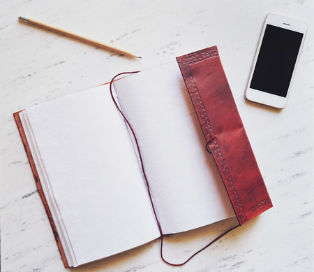 echnology: Top view of notepad, smartphone and pencil on marble background