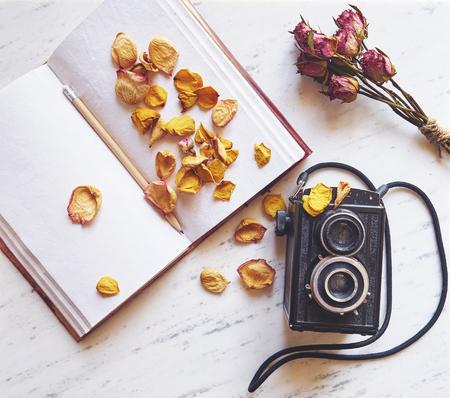 Uitstekende camera op marmeren achtergrond met lege notebook en gedroogde rozen