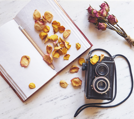 Vintage camera on marble background with blank notebook and dried roses Фото со стока