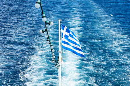 The Greek national flag flying from the stern of a ferry boat Stock Photo
