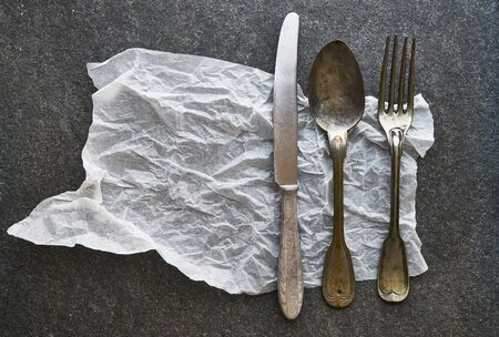 Vintage cutlery and baking paper on black marble background Stock Photo