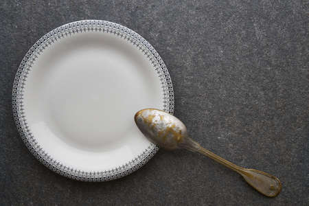 antique dishes: Vintage spoon and plate on black marble background Stock Photo