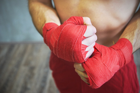 Shot of wrapped hands  with red boxing tape of young boxer fighter