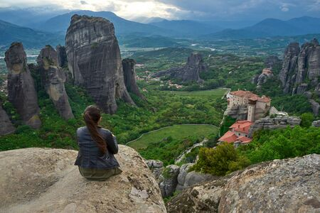 Girl enjoys the view of great and high rock in Meteora, Thessaly, Greece