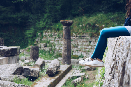 Girl is sitting on remains of a Doric temple, Mon Repos park, Corfu Town, Greece Stock Photo