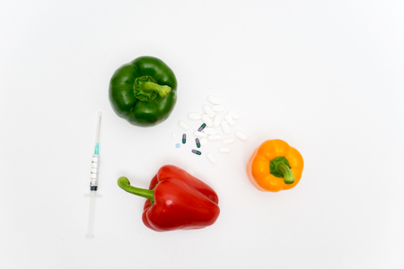 GMO concept on white background with  syringes, pills and peppers