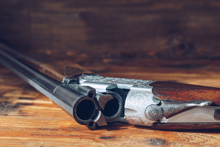 Open hunting rifle isolated on wooden background