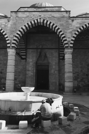 Ablution taps where a man washing his self before prayer time. Edirne Turkey.