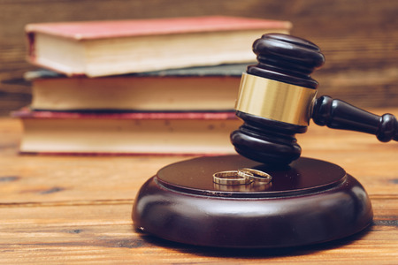 Wooden judge gavel and golden rings,  divorce concept Banque d'images