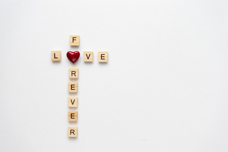 Wooden letters  spelling love for ever on white marble. Top view.