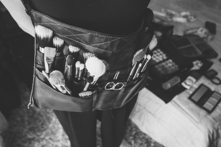 Professional makeup artist with a belt bag with makeup brushes. Stock Photo