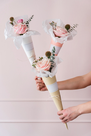 Womans hand holding paper cones with flowers