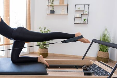 Young woman exercising on pilates reformer bed Фото со стока