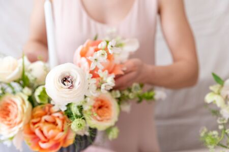 Woman hands touching a bouquet of flowers.