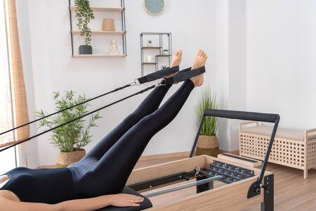 Young woman exercising on pilates reformer bed Stockfoto