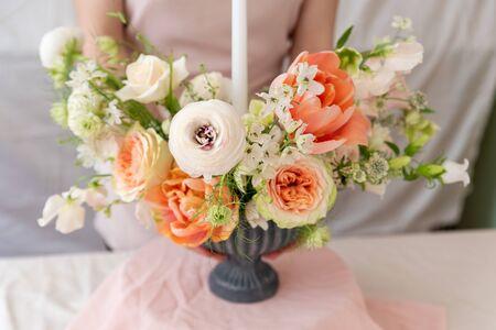 Woman holding vase full of flowers.