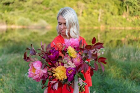 Beautiful young woman with flowers in the field and a lake as a background Фото со стока - 129025666