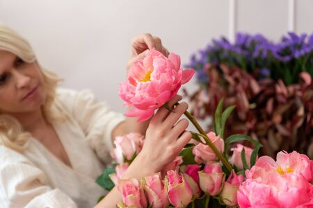 Hands of a beautiful young florist woman making modern bouquet of different flowers Фото со стока - 129025685